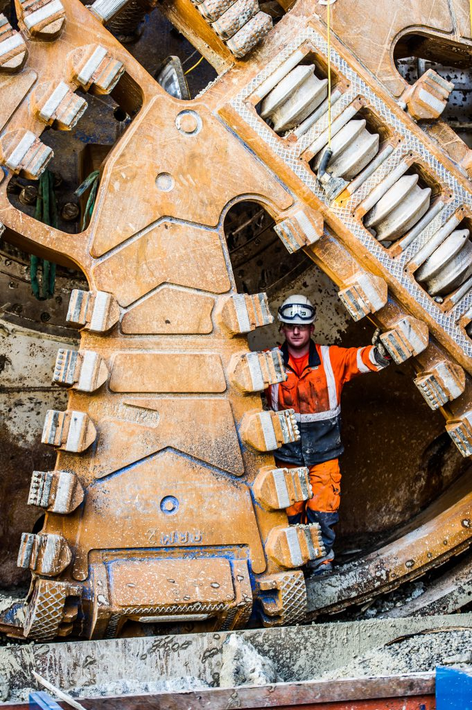 A tunnelling engineer emerges from the cutter head of TBM